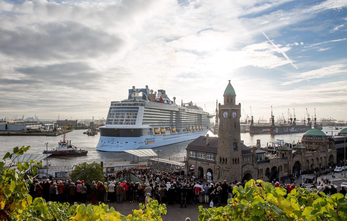 """Tausende Menschen betrachten das Kreuzfahrtschiff """"Quantum of the Seas"""", das in Hamburg vor den St. Pauli Landungsbrücken in ein Dock der Blohm & Voss AG eindockt. Foto: Axel Heimken/dpa"""